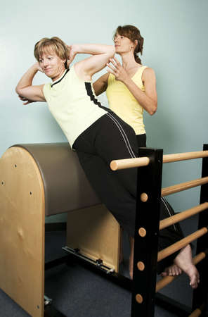 calisthenics: Personal Trainer Supervises a Woman Working Out on Equipment