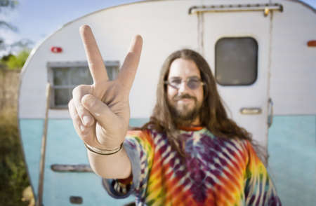 Friendly Hippie with Long Hair in Front of His Trailer making a peace Sign Stock Photo