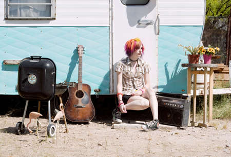 Punk girl with brightly colored hair sitting on a trailer step photo