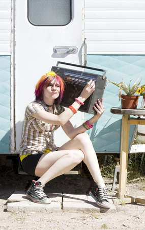 Rowdy: Punk girl with brightly colored hair sitting on trailer step holding boom box