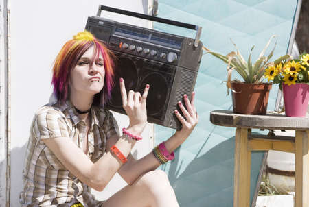 Punk girl with brightly colored hair sitting on trailer step holding boom box photo