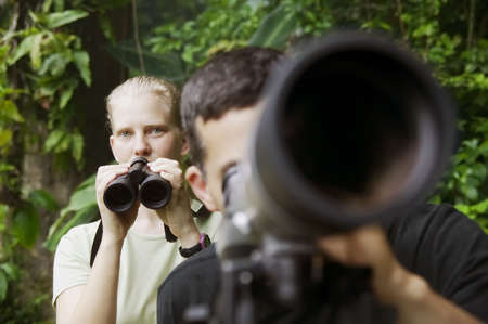 naturalist: Pretty Woman with Binoculars and Man with Telescope in Rain Forest Jungle Stock Photo