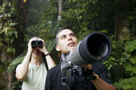 birdwatcher: Pretty Woman with Binoculars and Man with Telescope in Rain Forest Jungle Stock Photo