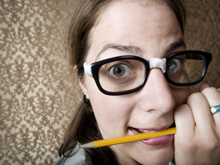 dweeb: Nervous nerdy Woman Chewing on a Yellow Pencil