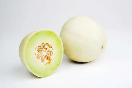 Two halves of a honeydew melon on a white background Stock Photo