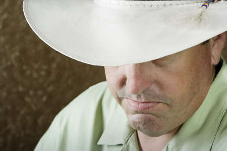 herdsman: Man beneath a white cowboy hat in front of a gold background Stock Photo