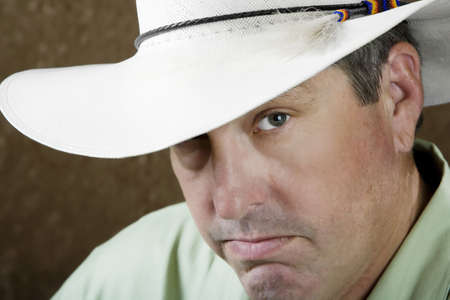 buckaroo: Man beneath a white cowboy hat in front of a gold background Stock Photo