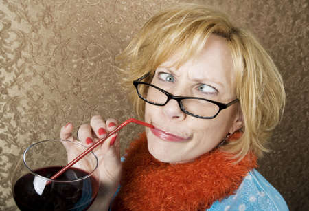 Crazy woman with crossed eyes drinking wine through a straw