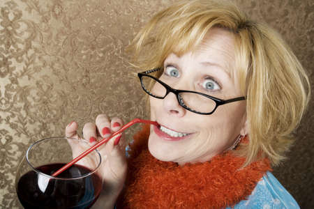 tawdry: Crazy woman with wild eyes drinking wine through a straw