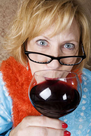 lurid: Crazy woman with wild eyes drinking wine  Stock Photo
