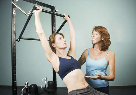 calisthenics: Athletic woman working out with a personal trainer Stock Photo
