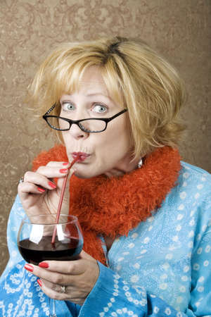 lurid: Funny woman drinking wine through a straw Stock Photo
