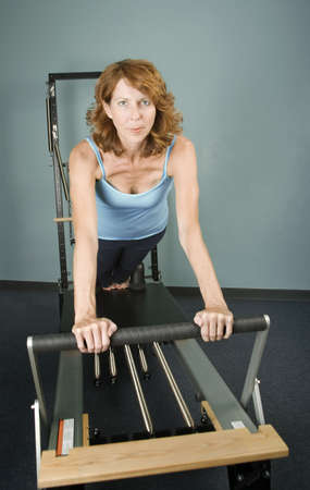 calisthenics: Pretty Woman Working Out on Pilates Equipment