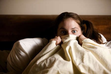 suspense: Frightened Woman in Bed with the Sheets Pulled Up to her Face