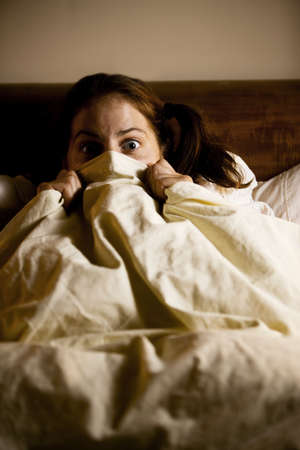 그녀의 얼굴을 뽑아 시트와 함께 침대에 겁 먹은 여자 스톡 콘텐츠