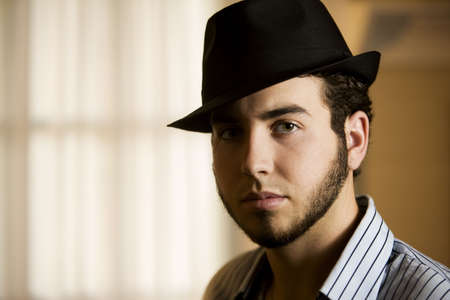 dapper: Handsome Young Man Indoors Wearing a Fedora Hat Stock Photo