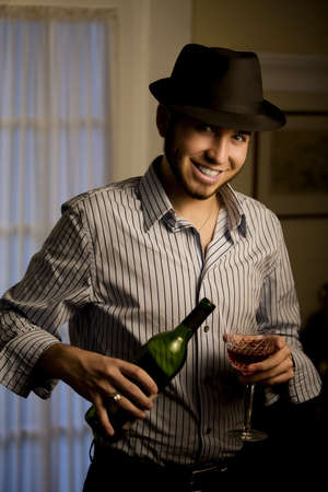 Handsome Young Man Indoors Wearing a Fedora Hat and Red Wine 写真素材