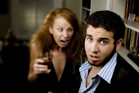 Young woman with cocktail yells at a man at party
