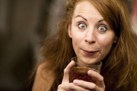 Woman with big eyes and hair sipping cocktail