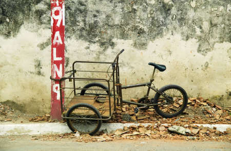 Tricycle chained to a red post roadside in Granada Nicaragua Banco de Imagens