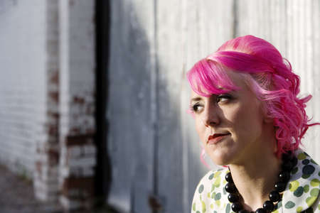 Woman with pink hair in an urban alley photo