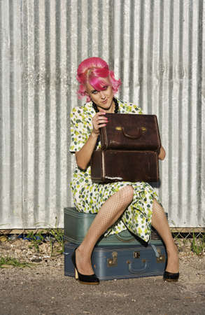 Woman with pink hair wearing polka dot dress in alley with suitcases photo