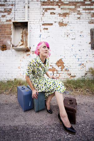 Woman with pink hair wearing polka dot dress in alley photo