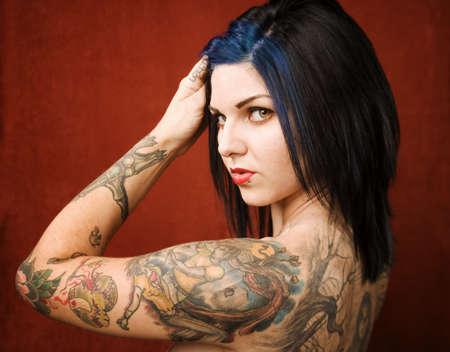 sexy tattoo: Pretty mujer joven con muchos tatuajes en su espalda y brazos  Foto de archivo