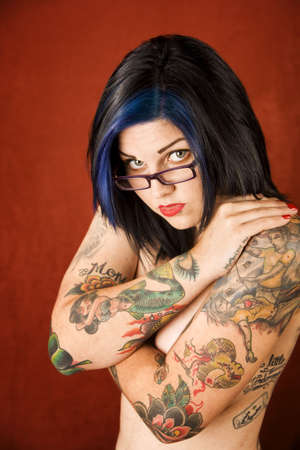 modesty: Pretty young woman with many tattoos crossing her arms Stock Photo