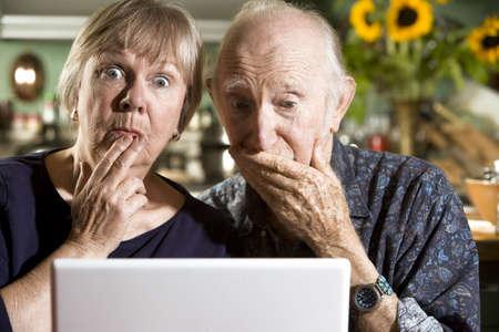 personnes �g�es: Perplexes Couple Senior dans leur salle � manger avec un ordinateur portable Banque d'images