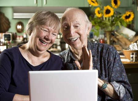 노트북 컴퓨터와 그들의 식당에서 수석 커플 웃 고 스톡 콘텐츠