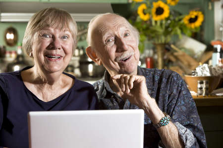 Smiling Senior Couple in their Dining Room with a Laptop Computer