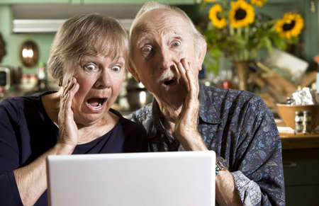 pornography: Shocked Senior Couple in their Dining Room with a Laptop Computer