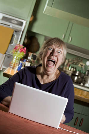pornography: Shocked Senior Woman in Dining Room with a Laptop Computer