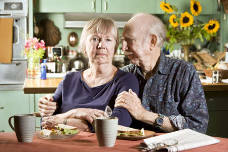 preoccupied: Portrait of Worried Senior Couple in their Dining Room Stock Photo