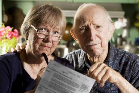 persona confundida: Pareja ancianos en el hogar con los proyectos de ley  Foto de archivo