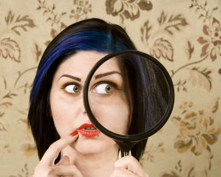 distort: Pretty Woman Holding a magnifying Glass to her Face Stock Photo