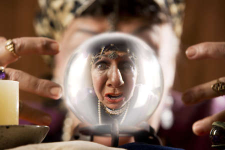 Female gypsy fortune teller looking into a crystal ball