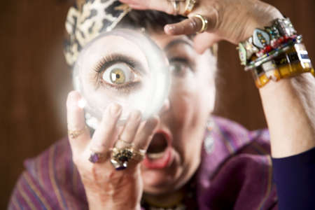 clairvoyant: Female gypsy fortune teller holding a crystal ball to her eye