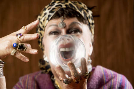 distort: Female gypsy fortune teller holding a crystal ball to her eye