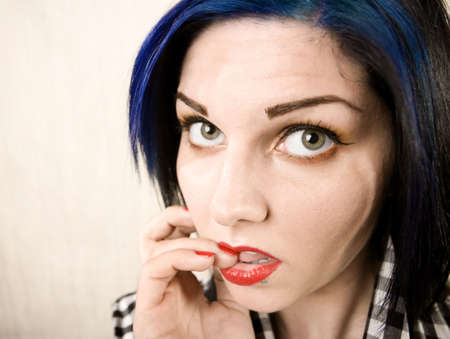 apprehensive: Wide angle portrait of an apprehensive rockabilly woman chewing her fingernail Stock Photo