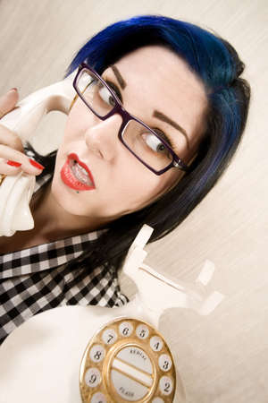 apprehensive: Apprehensive young woman talking on a vintage phone Stock Photo
