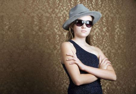 Jong meisje draagt een fedora en donkere zonnebril