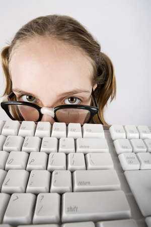 dweeb: Nerdy Young Girl Peeking Over a Computer Keyboard Stock Photo