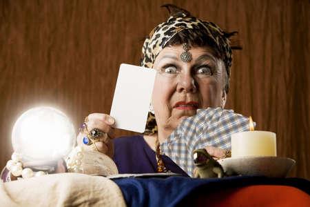 zigeunerin: Gypsy Wahrsagerin mit Kristallkugel, die eine leere Tarot-Karte Lizenzfreie Bilder