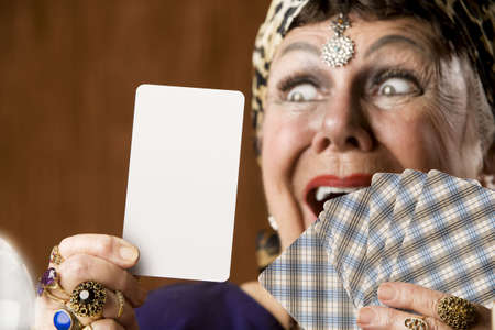 psychic: Gypsy fortune teller hiolding a blank tarot card Stock Photo