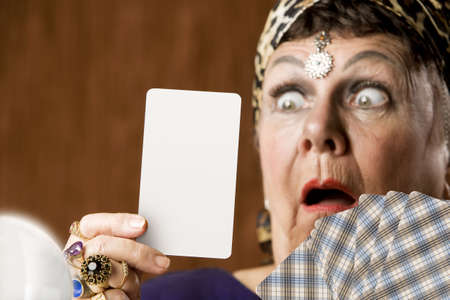 Gypsy fortune teller hiolding a blank tarot card Stock Photo
