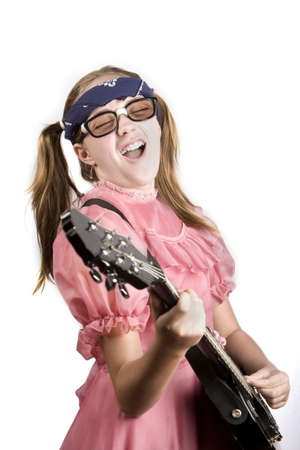 dork: Young girl in a pink dress with an electric rock guitar Stock Photo