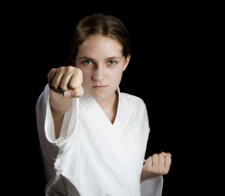 Pretty young girl in a karate pose on black background photo