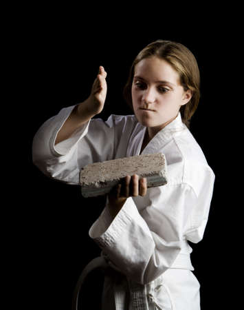 brick: Young girl karate chopping a brick on black background